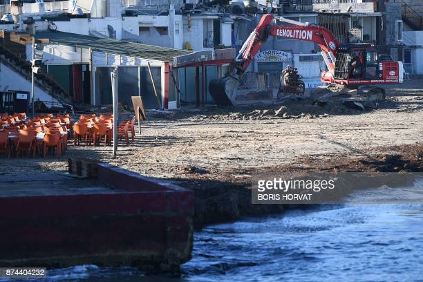 An excavator demolishes a restaurant that has been unrightfully erected on coastal terrain in Marseille southern France on November 15 2017 / AFP...