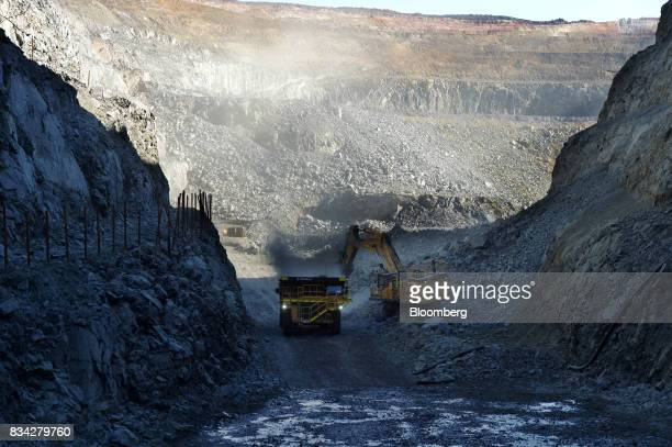 An excavator deposits ore into a dump truck in the White Foil open mine pit at Evolution Mining Ltd's gold operations in Mungari Australia on Tuesday...