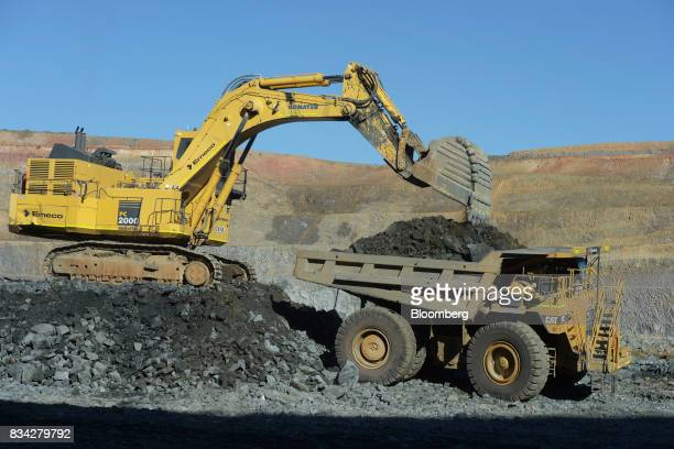 An excavator deposits ore into the back of a dump truck in the White Foil open mine pit at Evolution Mining Ltd's gold operations in Mungari...
