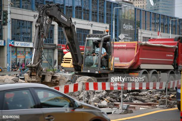 An excavator is seen diggin through rubble on a main road in Warsaw Poland on 4 August 2017