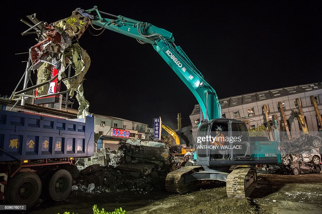An excavator is used to clear away rubble from a building (back R) which collapsed in the 6.4 magnitude earthquake, during the search and rescue operation in the southern Taiwanese city of Tainan early on February 9, 2016. A girl aged eight and three others were rescued Monday from the rubble of a Taiwan apartment tower complex, more than two days after it was felled by an earthquake, but over 100 others remain trapped in the ruins. / AFP / ANTHONY WALLACE