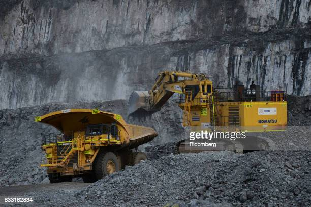 An excavator loads a dump truck in the Invincible open pit mine at the St Ives Gold Mine operated by Gold Fields Ltd in Kambalda Australia on...