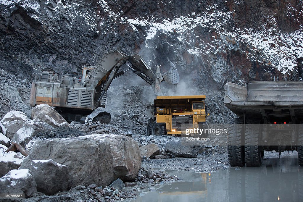 An excavator loads a dump truck with diamond ore at the base of the open pit at the Udachny diamond mine operated by OAO Alrosa in Udachny, Russia, on Sunday, Nov. 17, 2013. OAO Alrosa, the world's largest diamond producer, raised about $1.3 billion in an oversubscribed share sale from investors including Oppenheimer Funds Inc. and Lazard Ltd.'s asset-management unit, First Deputy Prime Minister Igor Shuvalov said. Photographer: Andrey Rudakov/Bloomberg via Getty Images