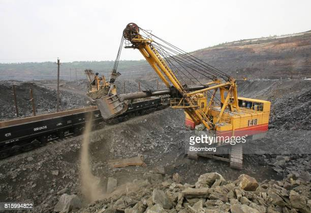 An excavator loads cargo wagons on a freight train with iron ore from the Lebedinsky GOK iron ore mining and processing plant operated by...