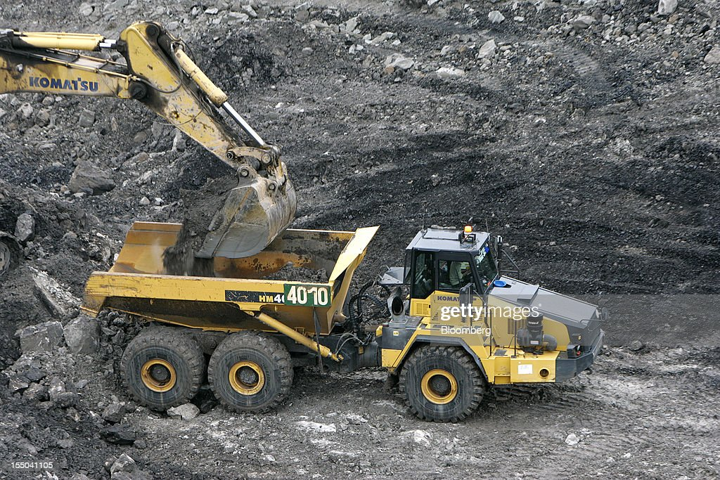 An excavator loads coal onto a truck in the open pit coal mine at the PT Exploitasi Energi Indonesia operations in Asam-Asam, South Kalimantan, Indonesia, on Monday Oct. 29, 2012. Indonesia, the world's largest exporter of coal for electricity generation, will reduce the amount of the fuel that producers must sell to buyers inside the country for next year by 9.4 percent. Photographer: Dadang Tri/Bloomberg via Getty Images