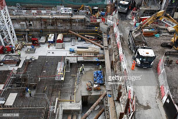 An excavator loads rubble into a truck as workmen install metal reinforcement rods to support concrete during building works at Balfour Beatty Plc's...