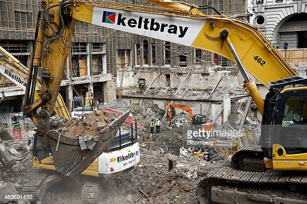 An excavator maneuvers rubble during building works at Balfour Beatty Plc's St James's Market construction site a joint Crown Estate and Oxford...