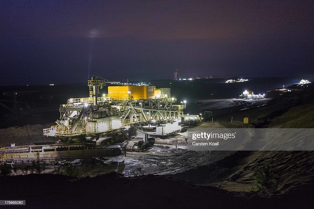 An excavator mines lignite coal at night in the Welzow open-pit lignite coal mine on August 10, 2013 near Welzow, Germany. The mine, operated by Vattenfall, is one of several in the immediate area that feed a nearby power plant with coal. In a development project initiated by state government, other nearby former open-pit mines have been turned into lakes in a rejuvenation effort that is also intended to make the area a viable tourist destination.