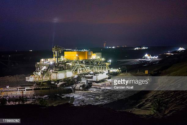 An excavator mines lignite coal at night in the Welzow openpit lignite coal mine on August 10 2013 near Welzow Germany The mine operated by...