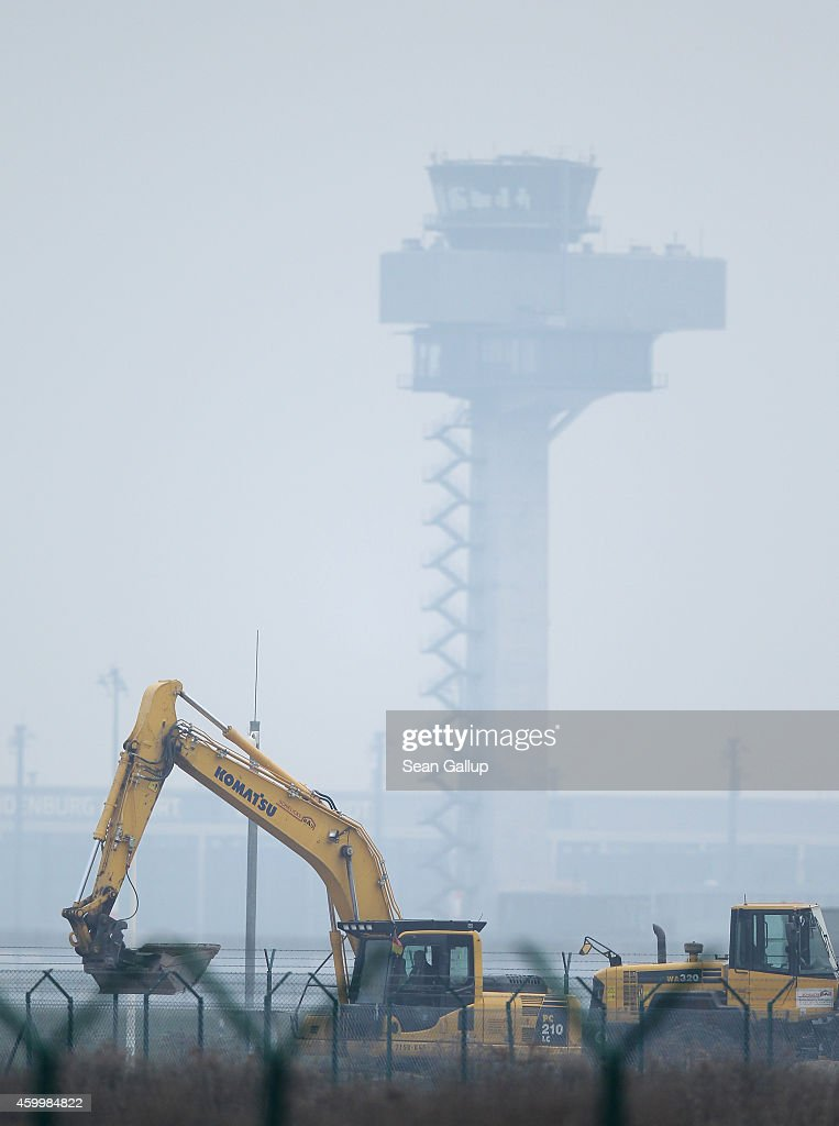 An excavator moves earth at a site next to the unfinished BER Willy Brandt Berlin Brandenburg International Airport as the airport's control tower stands behind on November 4, 2014 in Schoenefeld, Germany. The airport, originally scheduled to open in 2011, has been plagued by a massive design flaw in its fire safety system, cost overruns, delays and most recently a bribery scandal. Airport officials have not yet issued a firm new date for its opening.