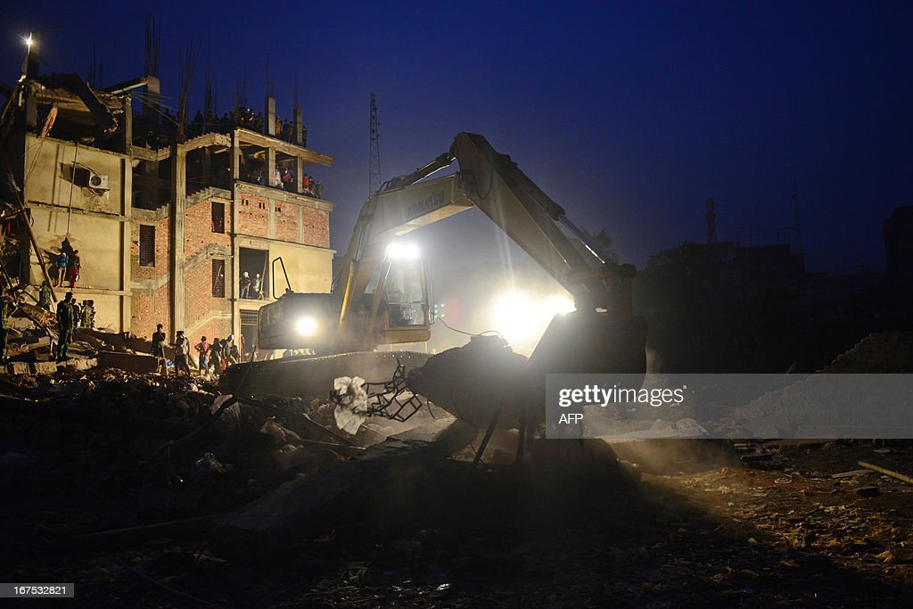 An excavator operated by the Bangladeshi Army removes debris as volunteers and rescue workers conduct rescue operations 60 hours after an eight-storey building collapsed in Savar, on the outskirts of Dhaka, on April 26, 2013. A total of 304 people are so far known to have died after the eight-storey building collapsed in the town of Savar on April 24. Rescuers are racing against time to find more survivors in searing temperatures, watched on by hundreds of anxious relatives waiting for news of their missing loved ones. AFP PHOTO/ MUNIR UZ ZAMAN