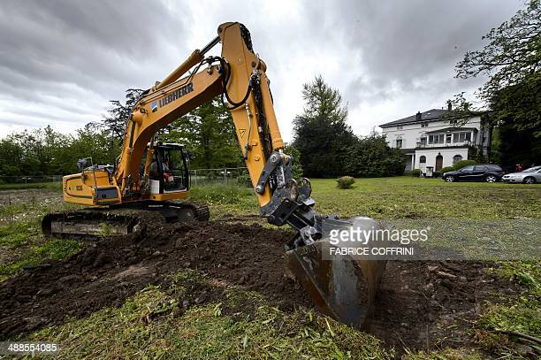 An excavator operates next to Charlie Chaplin's last residence the Manoir de Ban during the laying of the first brick of the Chaplin Museum on May 7...