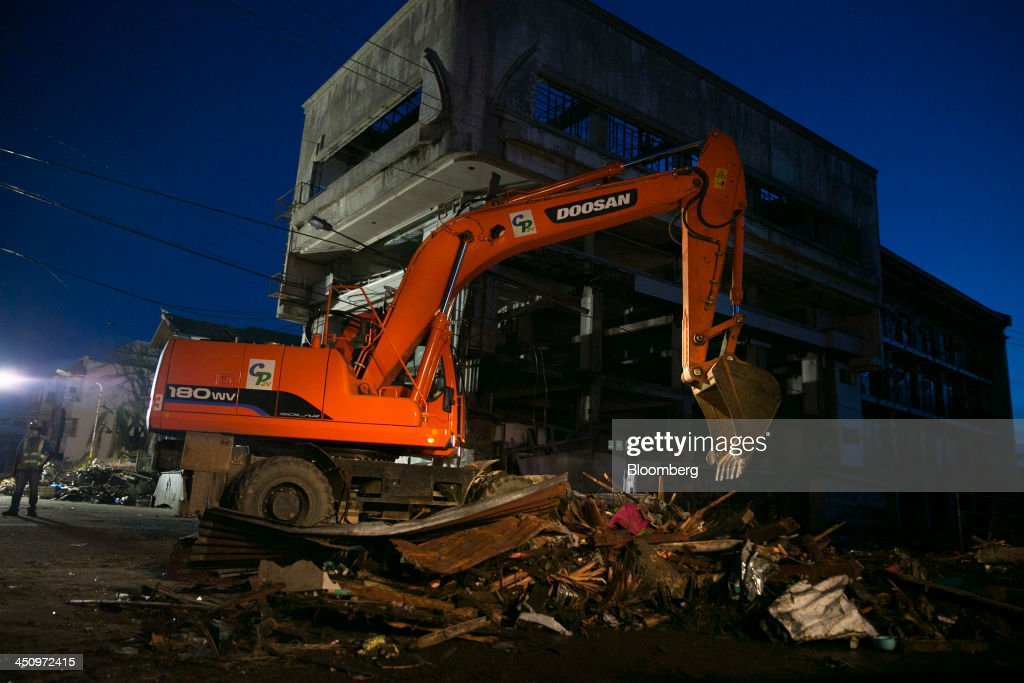 An excavator operates to clear debris at night in Tacloban, the Philippines, on Monday, Nov. 18, 2013. Super Typhoon Haiyan slammed into the central Philippines on Nov. 8, knocking down most buildings, killing thousands, displacing 4 million people and affecting more than 10 million. Photographer: Paula Bronstein/Bloomberg via Getty Images