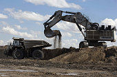 An excavator prepares to drop a load of earth into a dump truck at the Tavan Tolgoi coal deposit developed by Erdenes Tavan Tolgoi JSC a unit of...