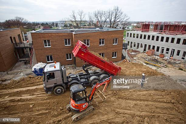 An excavator stands beside a truck as its openbox bed is raised by a hydraulic cylinder on the Vidailhan eco area residential construction site...