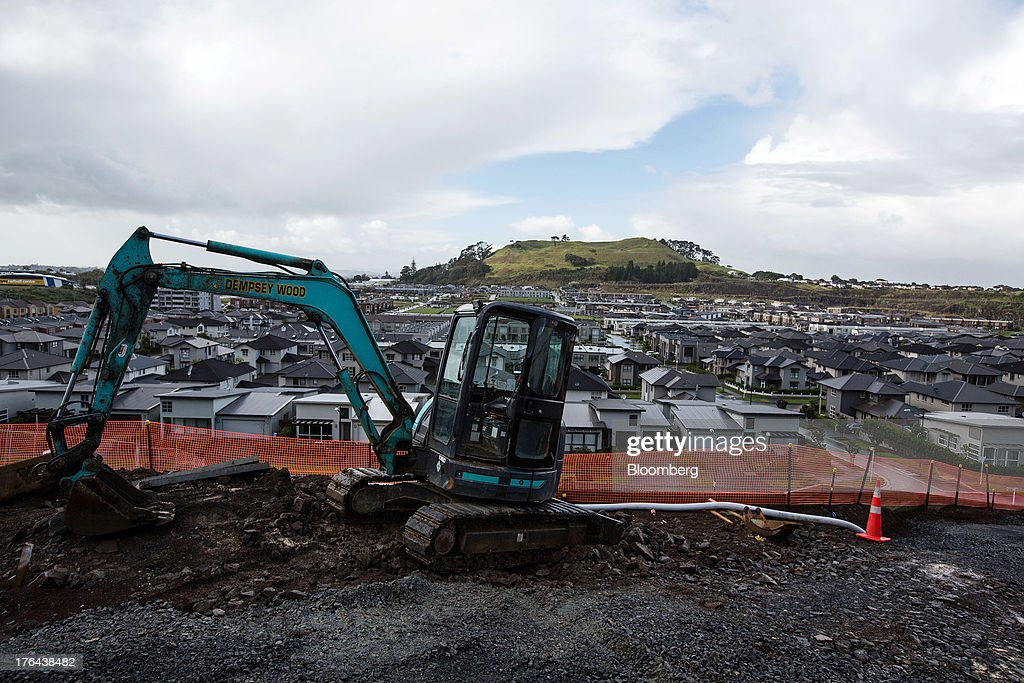An excavator stands on a construction site in front of houses in the suburb of Mount Wellington in Auckland, New Zealand, on Monday, Aug. 12, 2013. New Zealand's growth rate is forecast to outpace Australia's for the next two years, helping stem an exodus that's resulted in the highest proportion of its people living overseas in the developed world after Ireland. Photographer: Brendon O'Hagan/Bloomberg via Getty Images