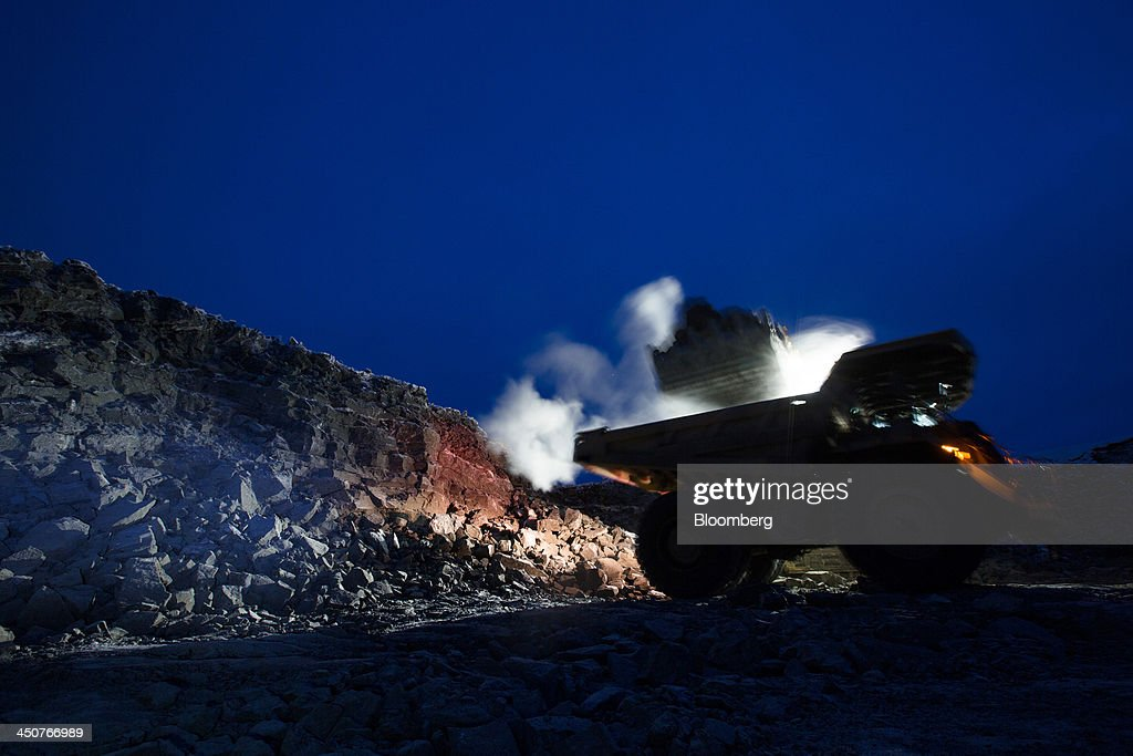 An excavator uses electric lights to illuminate diamond ore during night digging operations in the open pit at the Nyurbinsky diamond mine operated by OAO Alrosa in Nakyn, Russia, on Friday, Nov. 15, 2013. OAO Alrosa, the world's largest diamond producer, raised about $1.3 billion in an oversubscribed share sale from investors including Oppenheimer Funds Inc. and Lazard Ltd.'s asset-management unit, First Deputy Prime Minister Igor Shuvalov said. Photographer: Andrey Rudakov/Bloomberg via Getty Images