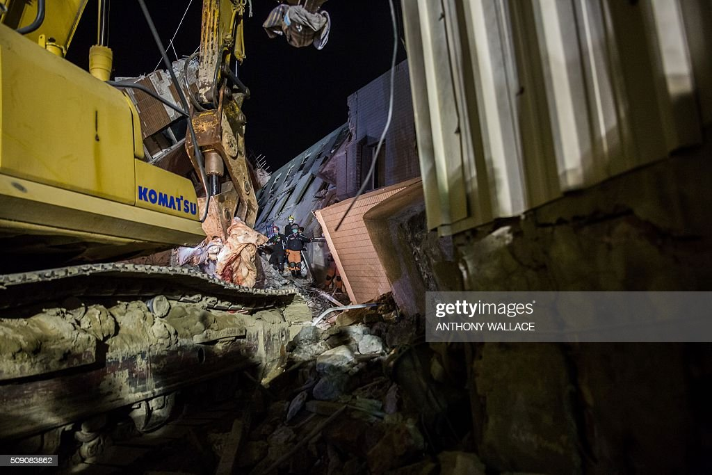 An excavator with a demolition pincer lifts out a bloodied duvet (centre L) as rescue workers dig a ditch to enable them to search under the remains of a building which collapsed in the 6.4 magnitude earthquake, in the southern Taiwanese city of Tainan early on February 9, 2016. Rescuers are set to start using diggers and extractors to remove giant concrete slabs once they have ensured all residents from the upper parts of the rubble have been freed. AFP PHOTO / ANTHONY WALLACE / AFP / ANTHONY WALLACE