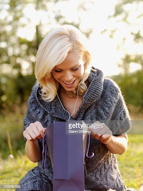 An excited woman looking into an open gift bag
