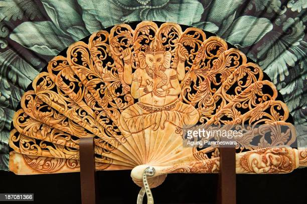 An exclusively produced hand fan with sticks and handles made from cow bone and decorated with Hindu deity Ganesha carved and painted by Balinese...