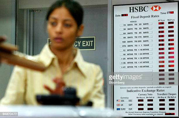 An executive at the HSBC Bank branch in New Delhi India works in front of a chart that displays Fixed Deposit rates Friday June 4 2004