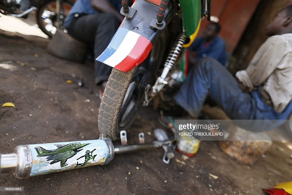 An exhaust muffler painted with a jet and a soldier lies near a scooter painted in the Malian and French colours in Bamako on March 12, 2013. French and Chadian forces are hunting Islamists rebels in northeastern Mali following a French-led intervention that drove the militants from cities in northern Mali they had seized last year.
