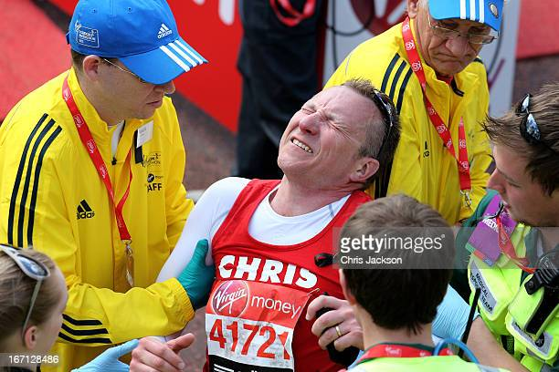 An exhausted competitor is assisted by race staff after crossing the finish line during the Virgin London Marathon 2013 on April 21 2013 in London...