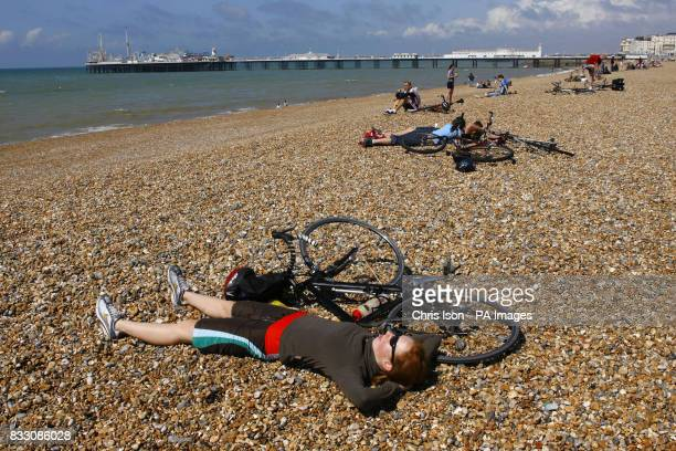 An exhausted competitor relaxes on the beach after arriving in Brighton after completing the British Heart Foundation London to Brighton Bike Ride