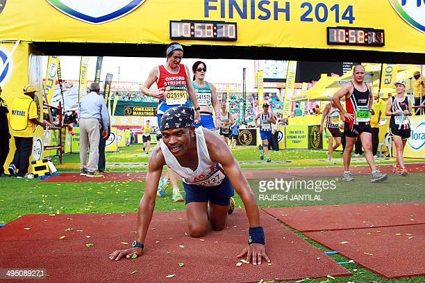 An exhausted Comrades Marathon runner collapses as he arrives at the finishing line at the end of the 89km Comrades Marathon between Pietermaritzburg...