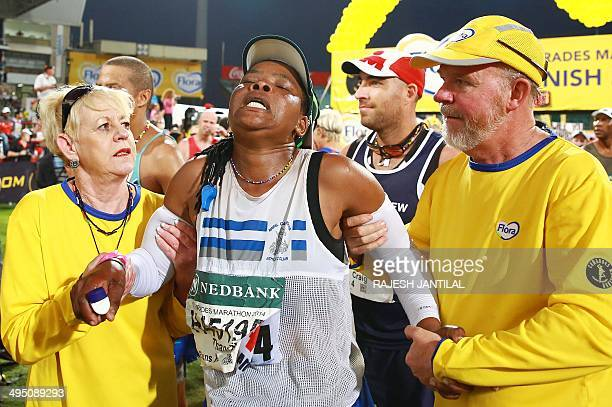 An exhausted Comrades Marathon runner is assisted after she crossed the finishing line at the end of the 89km Comrades Marathon between...