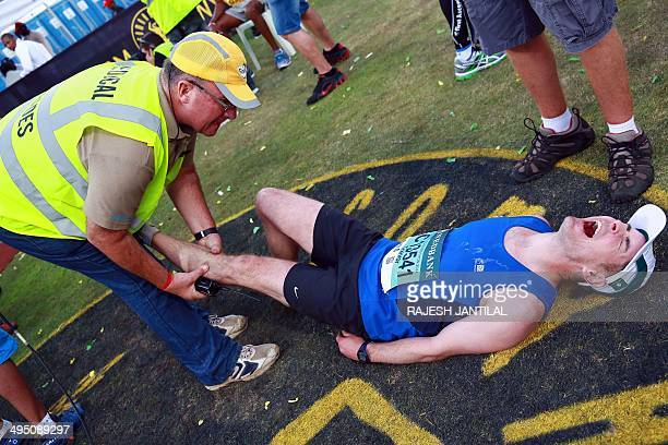 An exhausted Comrades Marathon runner is assisted by medical staff after he passed the finishing line at the end of the 89km Comrades Marathon...