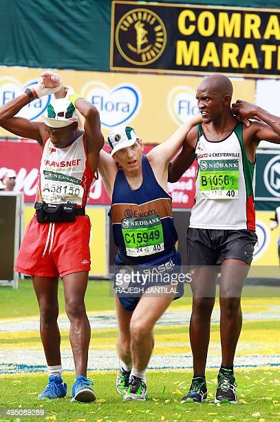 An exhausted Comrades Marathon runner is assisted by other runners after passing the finishing line at the end of the 89km Comrades Marathon between...
