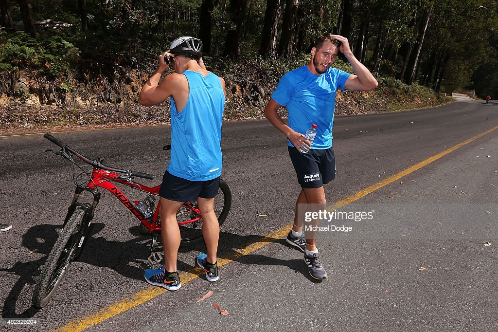 An exhausted Dale Thomas reacts handing his bike to a teamate at the half way chage over up Mount Buller during the Carlton Blues AFL training camp on January 27, 2015 in Mount Buller, Australia.