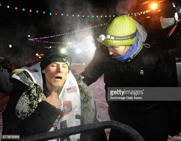 An exhausted Dallas Seavey collapsed on the back of sled after crossing under the burled arch in Nome Alaska to win the 2014 Iditarod Trail Sled Dog...