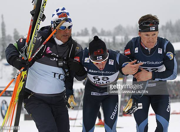 An exhausted gold winner Finland's Matti Heikkinen is helped out from the finish area by teammate Finland's Sami Jauhojaervi and an unidentified aide...