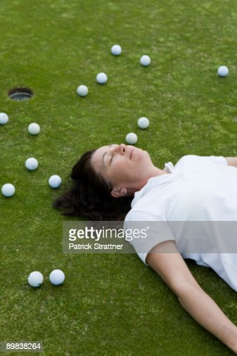 An exhausted golfer lying down on a golf course : Stock Photo