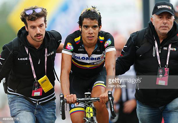 An exhausted Jarlinson Pantano of Colombia and team Colombia is helped by his team soigneurs after finishing in third place during the fourteenth...