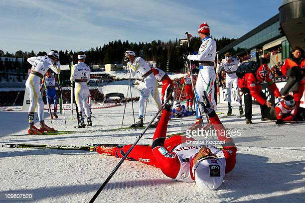 An exhausted Petter Northug of Norway celebrates on snow after crossing the finish line to win the gold medal in the Men's Cross Country 50km Mass...
