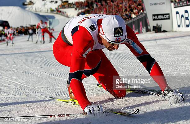 An exhausted Petter Northug of Norway collapses too the snow after crossing the finish line to win the gold medal in the Men's Cross Country 50km...