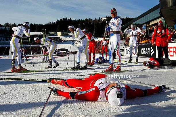 An exhausted Petter Northug of Norway lies on snow after crossing the finish line to win the gold medal in the Men's Cross Country 50km Mass Start...