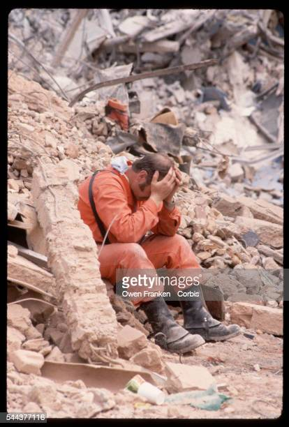 An exhausted rescue worker sits with his head in his hands amidst rubble of the 1985 earthquake in Mexico City Mexico