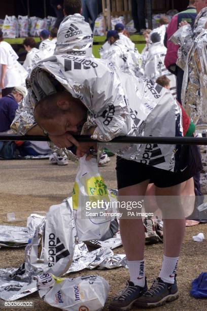 An exhausted runner takes a well earned rest at the end of the Flora London Marathon 2000 in London