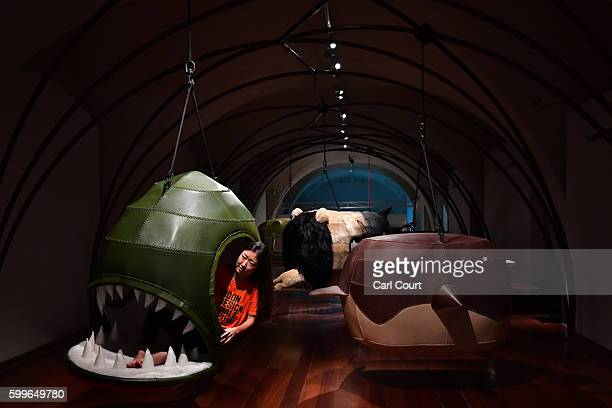 An exhibition assistant poses for photographs in 'Piranha 1 Nerina' part of installation by Porky Hefer who is representing South Africa at the...
