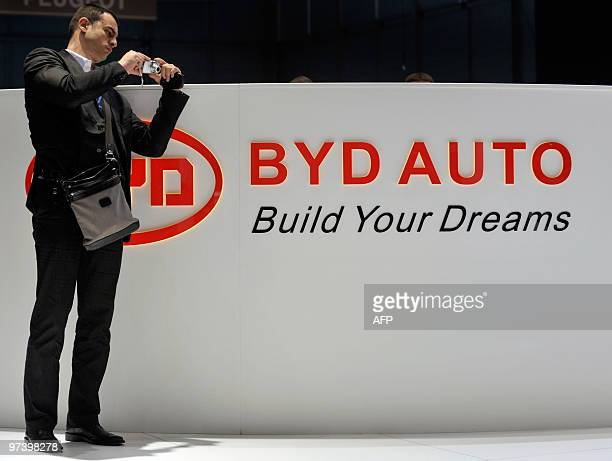 An exhibition visitor takes a photo next to the logo of Chinese car manufacturer BYD at the 80th Geneva International Motor Show at Palexpo in Geneva...
