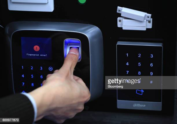 An exhibitor demonstrates a fingerprint scanning device on a display of Alhua Technology video intercom products in the Zheijiang Dahua Technology Co...