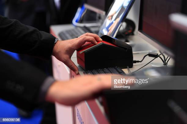 An exhibitor demonstrates the Dermalog LF10 biometric fingerprint scanning device right while another uses a passport scanner at the Dermalog...