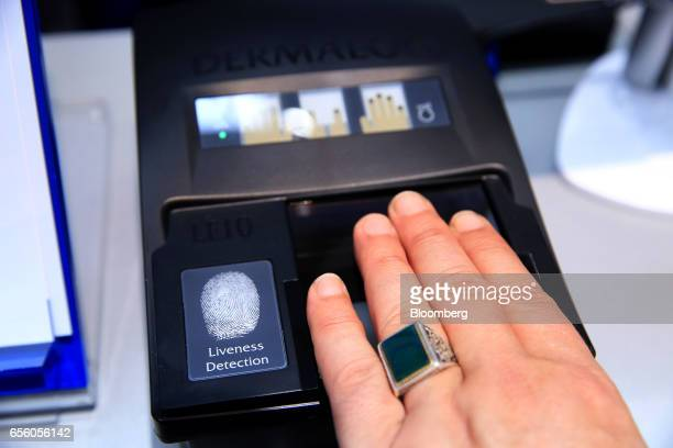 An exhibitor demonstrates the Dermalog LF10 biometric fingerprint scanning device at the Dermalog Identification Systems GmbH pavilion at the CeBIT...