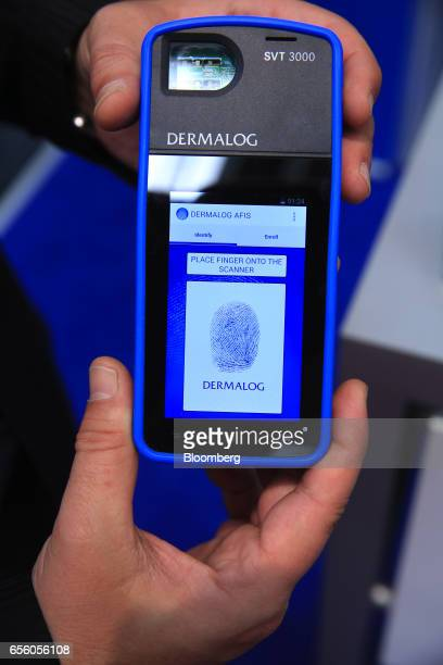 An exhibitor demonstrates the fingerprint scanning functions of a handheld Smart Verification Terminal SVT3000 device in the Dermalog Identification...