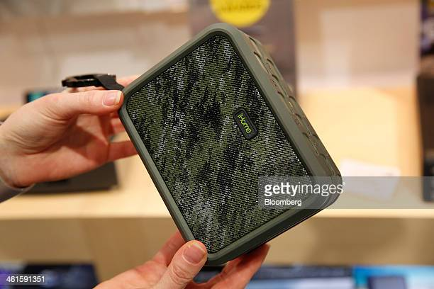 An exhibitor displays an iHome iPX2 waterproof rechargeable speaker for a photograph at the SDI Technologies Inc booth during the 2014 Consumer...