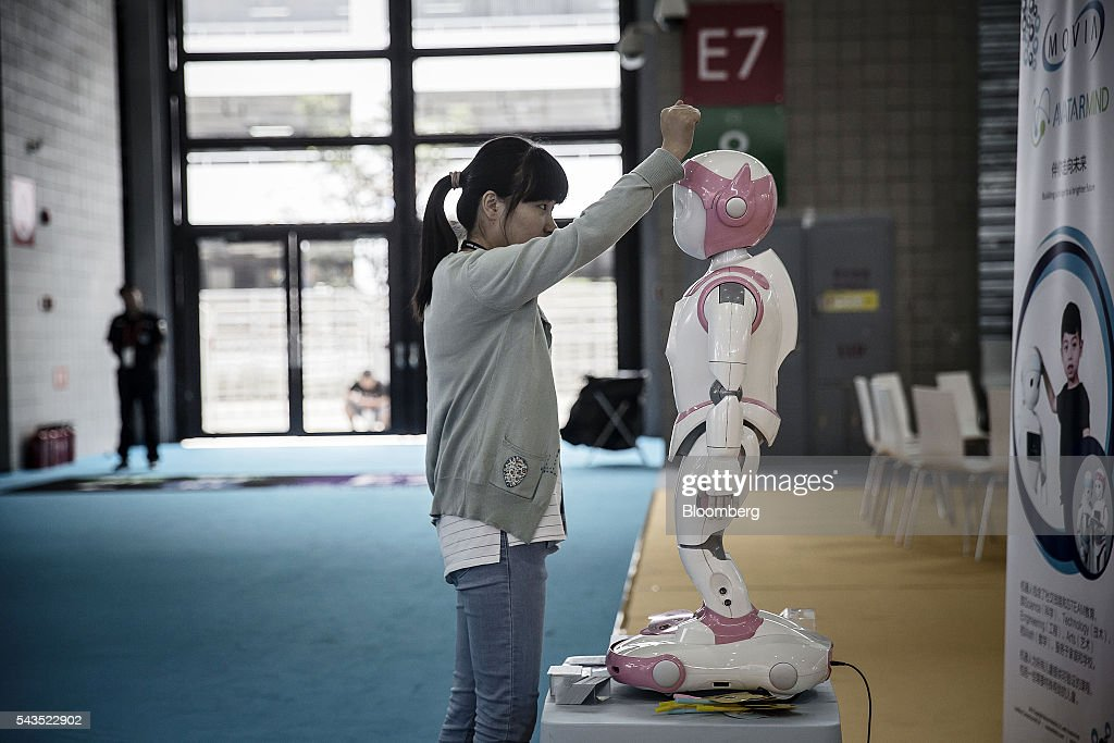 An exhibitor dusts off a robot on display at the Mobile World Congress Shanghai in Shanghai, China, on Wednesday, June 29, 2016. The exhibition runs until July 1. Photographer: Qilai Shen/Bloomberg via Getty Images